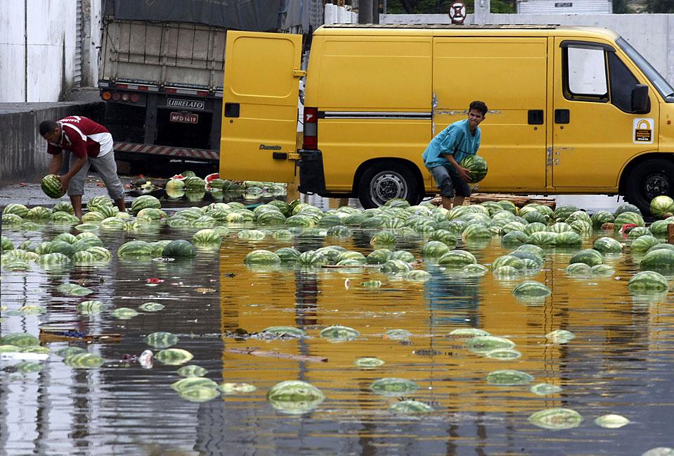 8) Люди собрают арбузы на затопленном на фруктовом рынке в Сан-Пауло, Бразилия. Из-за проливных дождей две главных реки Сан-Пауло вышли из берегов, блокируя главные дороги. По сообщениям местных СМИ, в результате оползня шесть человек погибли. (Paulo Whitaker/Reuters)