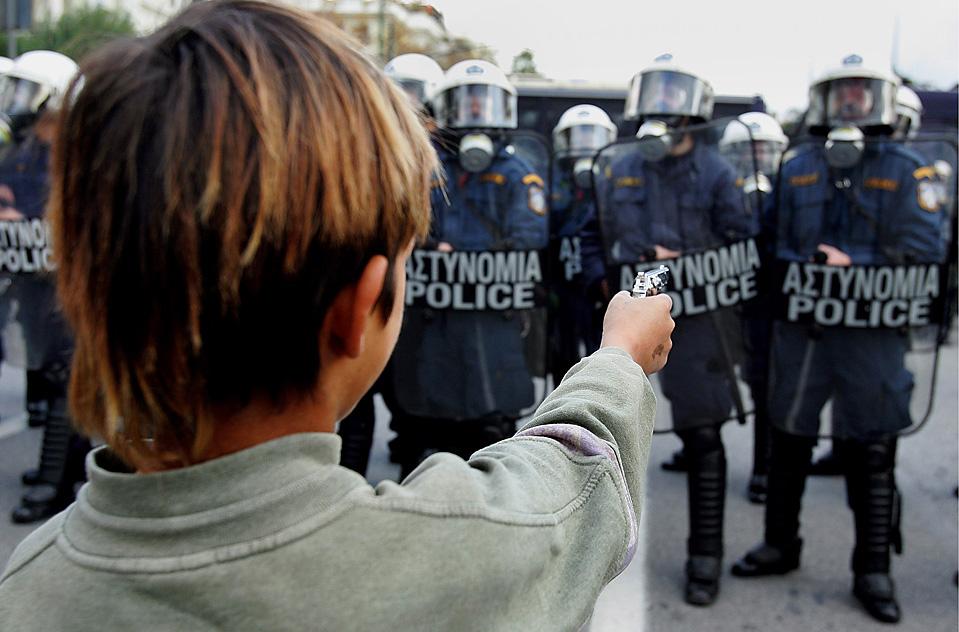 7) Мальчик целится из игрушечного пистолета в греческих полициейских во время мирной демонстрации в центре Афин. Демонстрация была проведена спустя четыре дня после первой годовщины убийства подростка полицией в прошлом году. (Simela Pantzartzi/EPA)