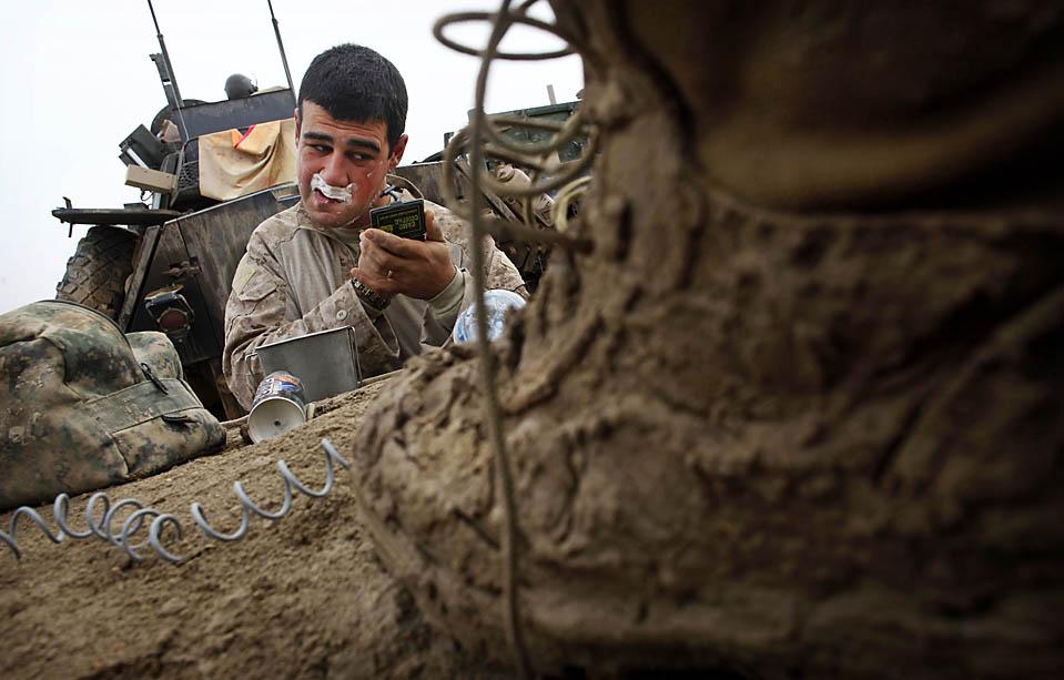 1) Капрал морской пехоты США Александр Александров из Мэриленда бреется на военноей базе в Хан Нешин, в неспокойной провинции Гильменд на юге Афганистана (AP Photo/Kevin Frayer)