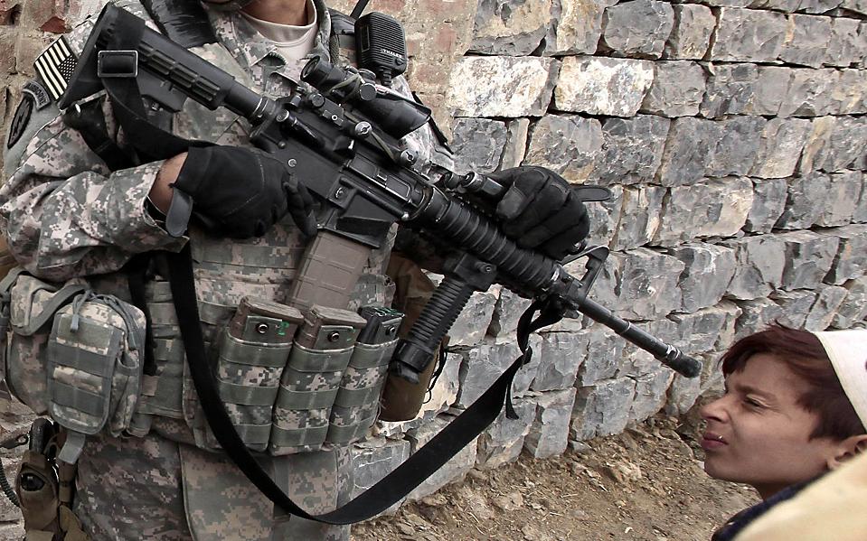 2) Мальчик заглядывает в ствол автомата солдата армии США, в то время как тот патрулирует Шембавут в Афганистане. Второй по рангу американский генерал в Афганистане, в понедельник заявил, что увеличение военного контингента в стране может занять больше времени, чем ожидалось. Вероятней всего это займет от девяти до одиннадцати месяцев. (Zohra Bensemra/Reuters)