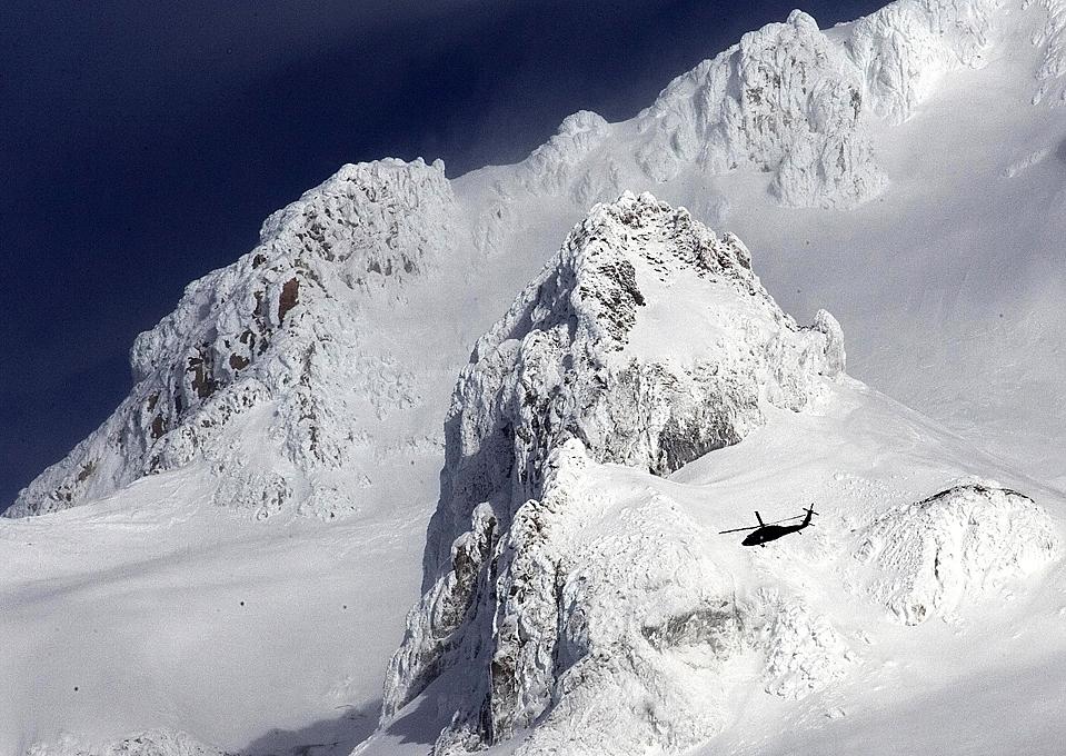7) Вертолет пролетает мимо скалы «Иллюминация» на возвышенности горы Орегон в поисках двух пропавших альпинистов, один из которых был найден мертвым.. (Don Ryan/Associated Press)