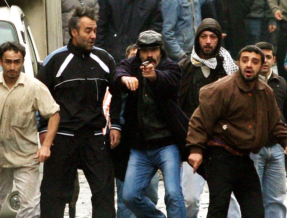 10) Турецкие националисты стреляют из огнестрельного оружия в ходе столкновений с курдскими активистами в Стамбуле. Курды провели акции протеста против решения суда о роспуске единственной партии курдов в парламенте Турции, Партии демократического общества. (Bulent Kilic/Agence France-Presse/Getty Images)