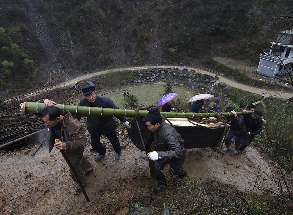 11) Сельские жители несут гроб жертвы стрельбы в Анхуа, китайской провинции Хунань. Полиция говорит, что  арестовала Лю Айбинга, психически больного человека, которого обвиняют, том, что в субботу он застрелил из дробовика 12 человек, включая своего отца. (Associated Press)