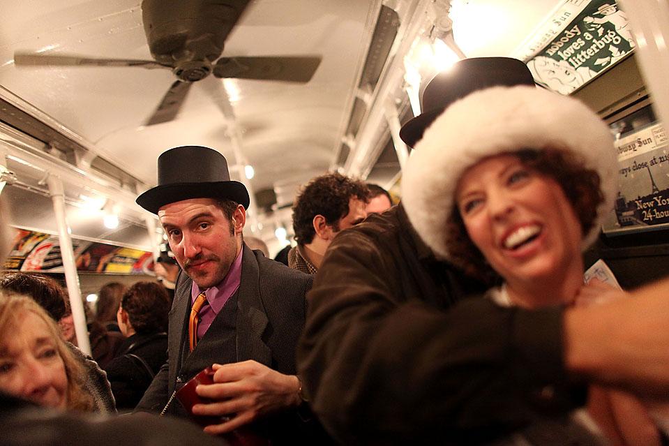 12) Участники вечеринки «Винтажное чаепитие» в костюмах едут в старинном поезде метро. Это мероприятие было организовано тургруппой «Levys' Unique New York» в Нью-Йорке. Весь декабрь этого года каждое воскресенье из Манхэттена в Квинс в Нью-Йорке курсирует поезд метро «Нью-Йорк Сити Транзит», в котором установлены старинные потолочные вентиляторы и плетеные сиденья. (Mario Tama/Getty Images)