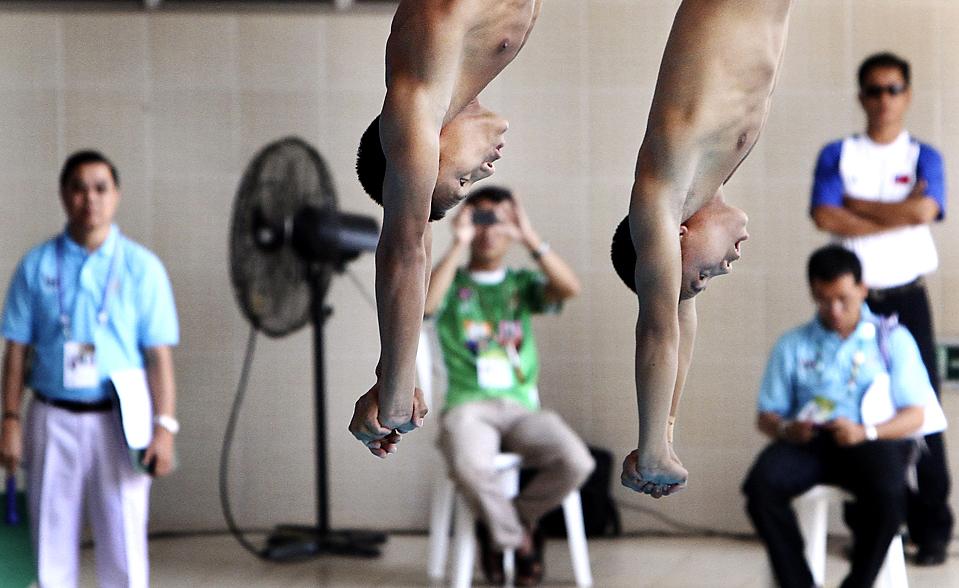 14) Спортсмены из Мьянмы Наунг Киа и Ний Тун во время мужских соревнований по синхронным прыжкам с 10-метровой вышки во время Игр Юго-Восточной Азии в Вьентьян, Лаос. (Wong Maye-E./Associated Press)