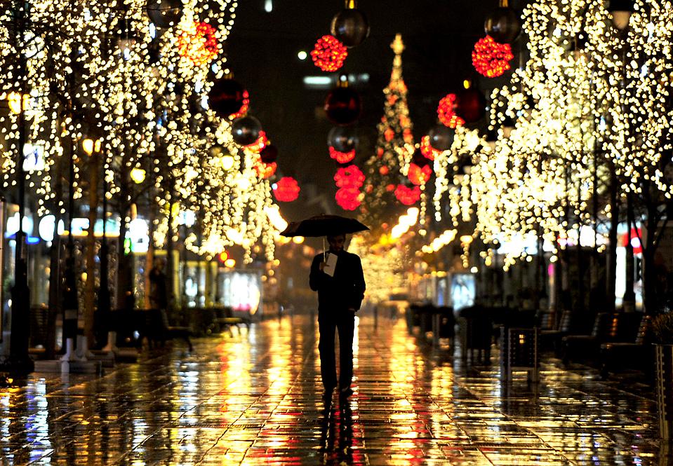 6) Человек проходит по аллее деревьев освещенных праздничными огнями в Скопье, Македония. (Ognen Teofilovski/Reuters)