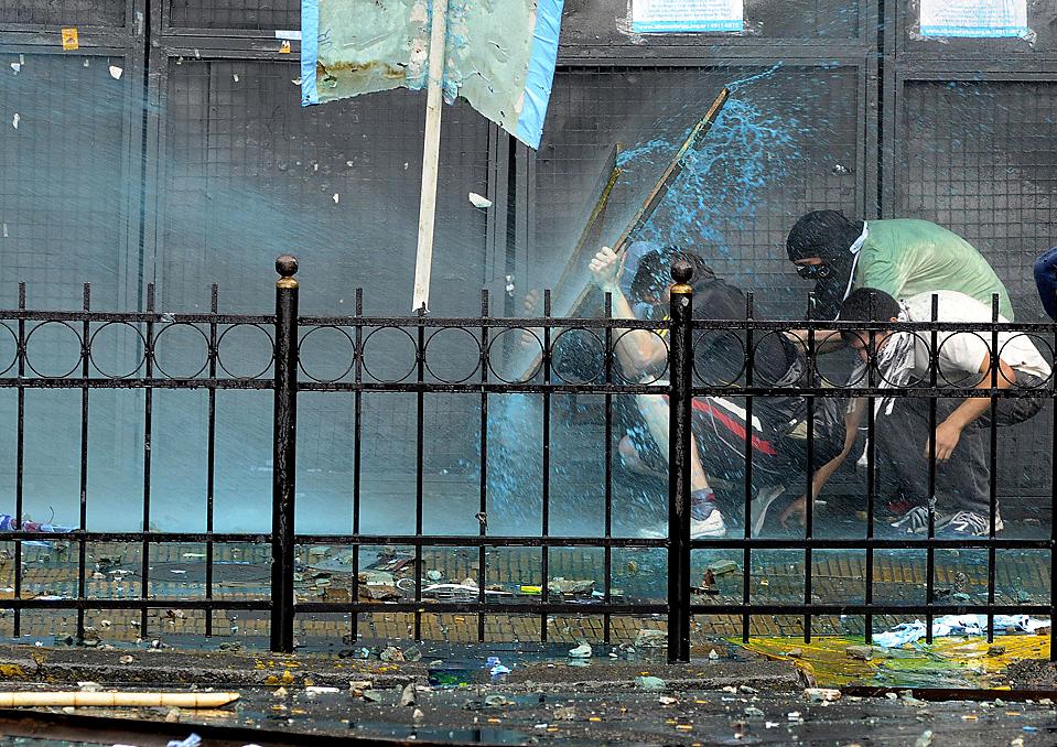 8) Студенты закрываются от струй воды из водяных пушек, которые применила против них полиция во время столкновений, причиной которых стали протесты против переизбрания ректора Университета Буэнос-Айреса. Студенты выступали против того, что в Совете, который избрал ректора не было достаточного количества представителей студенчества. (Rolando Andrade/Associated Press)