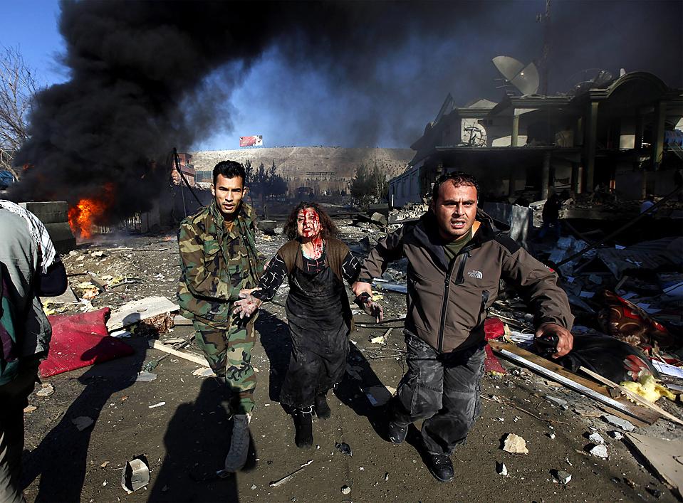 11) Потерпевшую уводят с места взрыва в Кабуле. Во взрыве двух автомобилей, начиненных взрывчаткой, погибли, по меньшей мере, 14 человек, в том числе и сам террорист-смертник, который вероятней всего хотел убить бывшего вице-президента страны. (Ahmad Masood/Reuters)