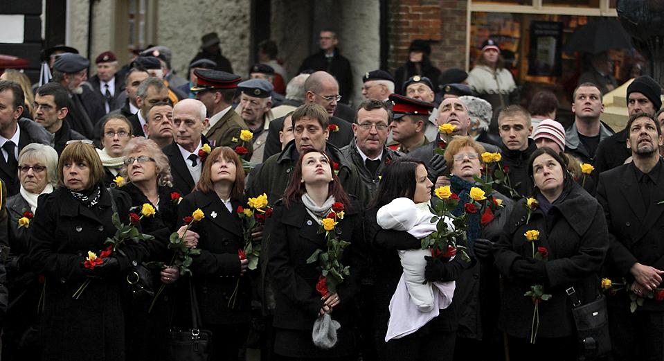 12) Скорбящие родственники и друзья смотрят на самолет, пролетающий над английским городом Вуттон Бассетт, в ожидании катафалка с телом капрала Адама Дрейна. 23-летний капрал был убит 7 декабря на контрольно-пропускном пункте в афганской провинции Гильменд. Он стал сотым британским военнослужащим, который погиб в этом году в Афганистане. (Matt Dunham/Associated Press)