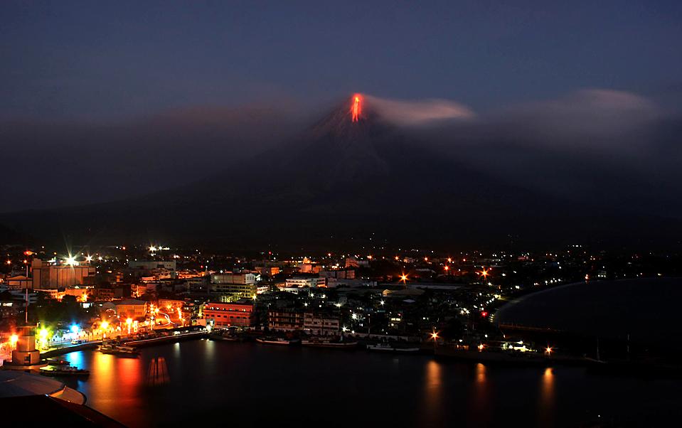 13) Из самого активного вулкана на Филиппинах, Майон, начинает выходить лава и струи пепла. Этот снимок был сделан в Легаспи во вторник. Более 20 тысяч человек уже были эвакуированы. Последнее извержение вулкана Майон произошло в 2006 году. Во время него пришлось эвакуировать около 30 тысяч человек. А во время извержения 1993-го года погибли 79 человек. (Charism Sayat/Agence France-Presse/Getty Images)