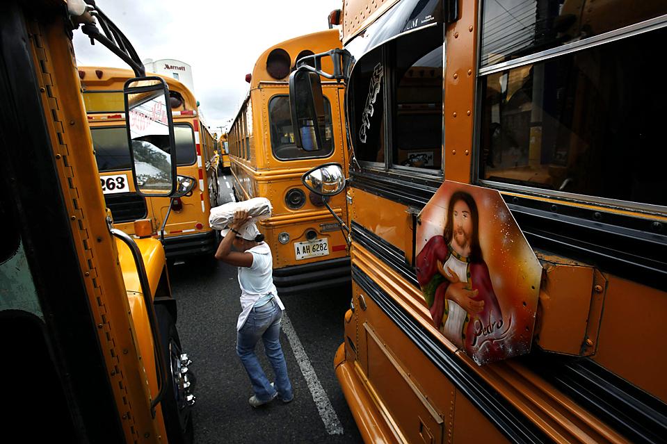 16) Уличная торговка проходит между автобусами во время забастовки в Тегусигальпе, Гондурас. Водители автобусов устроили забастовку с требованием к правительству субсидировать стоимость тарифов на проезд. (Esteban Felix/Associated Press)