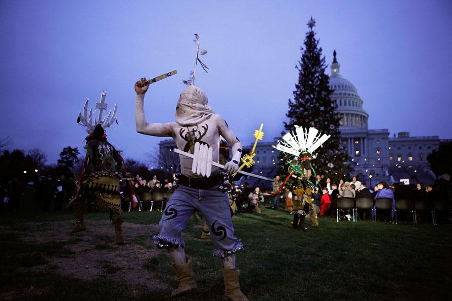 12. Танцоры племени апачей Белых гор из резервации Форт Апачи в Аризоне танцуют на церемонии зажжения новогодней елки у Капитолия в Вашингтоне, округ Колумбия. (Photo by Chip Somodevilla/Getty Images)