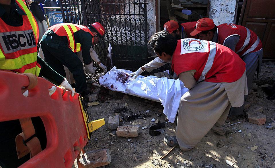 8) Спасатели уносят труп с места теракта у здания пресс-клуба в Пешаваре, Пакистан. В результате этого взрыва, по меньшей мере, три человека были убиты и 17 ранены. (Fayaz Aziz/Reuters)