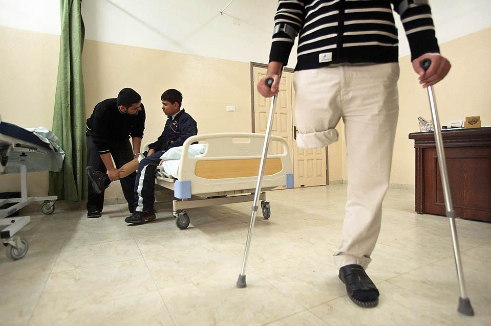 9) Моате Абу Рабих сидит на кровати в отделении физической терапии в Бейт-Лахии, сектор Газа. Этот 13-летний палестинец потерял ногу во время израильского наступления, которое началось в декабре прошлого года. Тогда было убито более 1000 палестинцев и, по меньшей мере, 13 израильтян. (Suhaib Salem/Reuters)