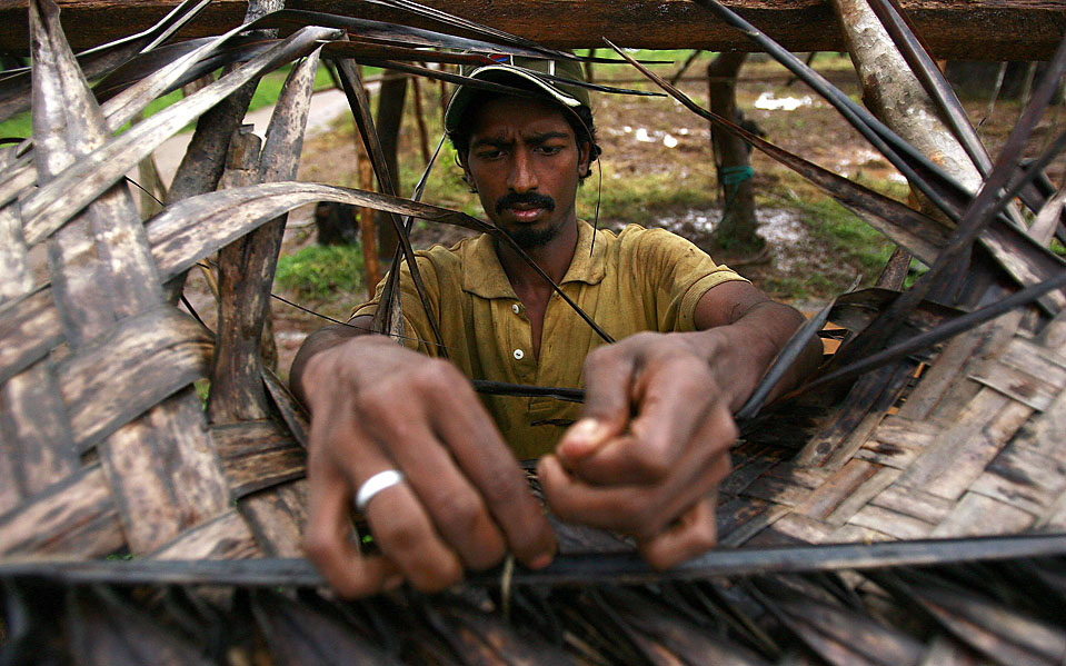 12) Этнический тамил 25-летний Шибешен Гинеш, связывает части крыши в лагере для беженцев вблизи Вавунии на Шри-Ланке. Правительство переселило гражданских лиц из-за боевых действий во время длительной гражданской войны. (Andrew Caballero-Reynolds/Reuters)