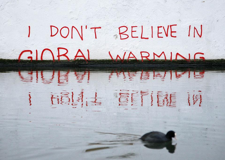 """14) Фраза """"Я не верю в глобальное потепление"""" написана на стене рядом с каналом Риджентс в Лондоне. Британские СМИ полагают, что авторство этого граффити принадлежит уличному художнику Бэнкси. (Luke MacGregor/Reuters)"""