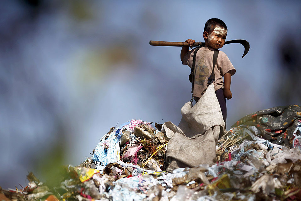 15) Мальчик из Мьянмы собирает пластик на мусорной свалке вблизи тайского города Мае Сот. Несколько сотен нелегальных иммигрантов живут в этом приграничном городе, приехав сюда в поисках лучшей жизни. (Damir Sagolj/Reuters)