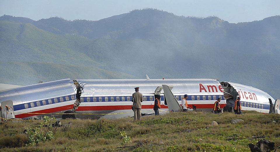 3) Рабочие разбирают мусор вокруг обломков фюзеляжа самолета авиакомпании American Airlines из Майами, который сошел с взлетно-посадочной полосы международного аэропорта, в Кингстоне, Ямайка. В результате аварии пострадало более 40 человек. (Lloyd Robinson/Associated Press)