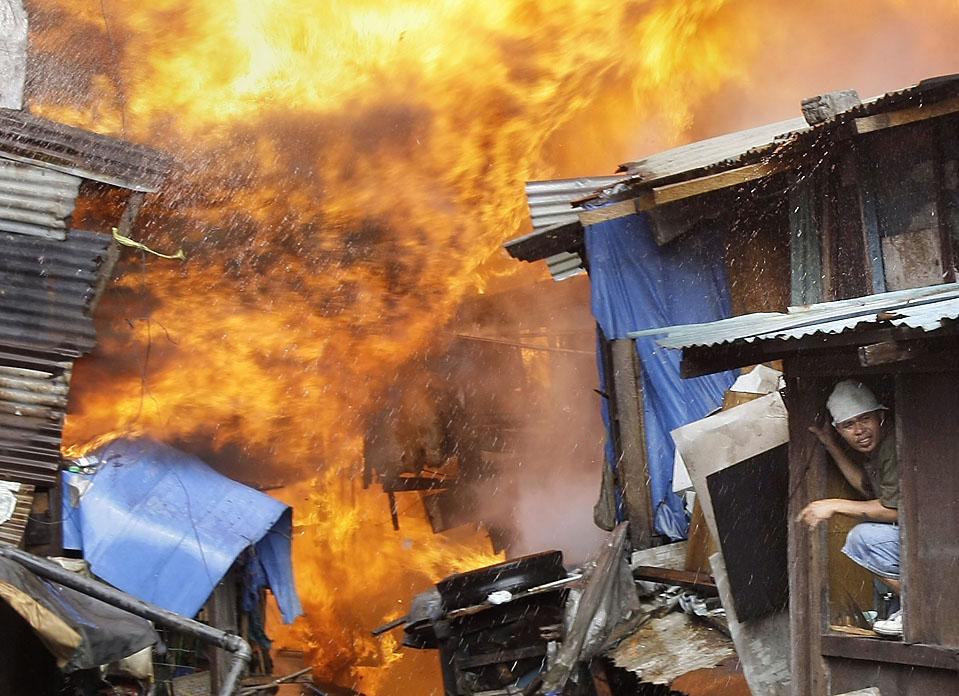 5) Человек выглядывает из окна в пригородном районе Пасай, расположенном к югу от Манилы, Филиппины, во время огромного пожара, в результате которого выгорели ряды лачуг в районе. (Pat Roque/Associated Press)