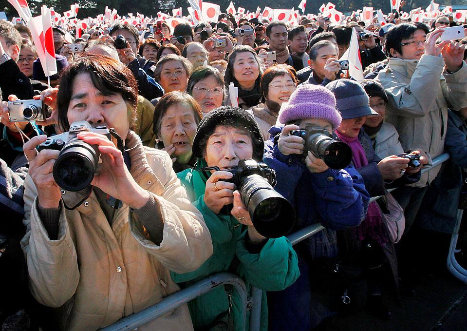 14) Люди фотографируют императора Акихито во время его публичного выступления, проводимого в честь его 76-летия в императорском дворце в Токио. (Itsuo Inouye/Associated Press)