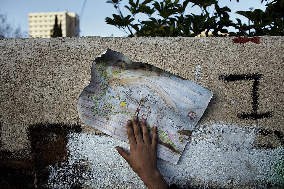 15) Палестинский мальчик держит рисунок, прислонив его к стене одного домов, в котором жили израильские поселенцы в районе Шейх-Джарра в Восточном Иерусалиме. (Marco Longari/AFP/Getty Images)