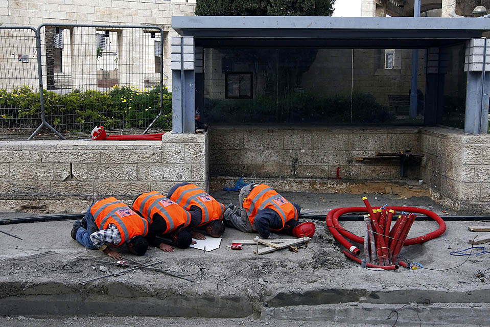 2. Мусульманские рабочие молятся на месте строительства остановки трамвая в Иерусалиме. Трамвай, пути для которого они прокладывают, будет ездить по Иерусалиму и его окрестностям. (Abir Sultan/European Pressphoto Agency)