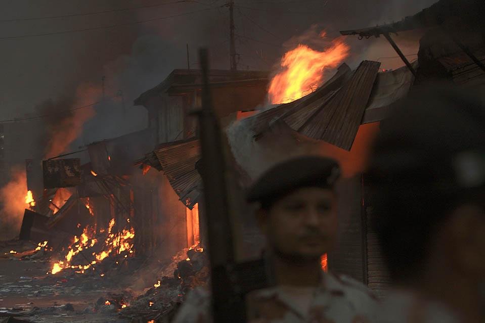 3. Солдаты охраняют магазины в Карачи, Пакистан, подожженные шиитскими мусульманами после того, как террорист-смертник ворвался в процессию, которая проходила в честь шиитского священного дня Ашура. В результате было убито, по меньшей мере, 30 человек. (Shakil Adil/Associated Press)