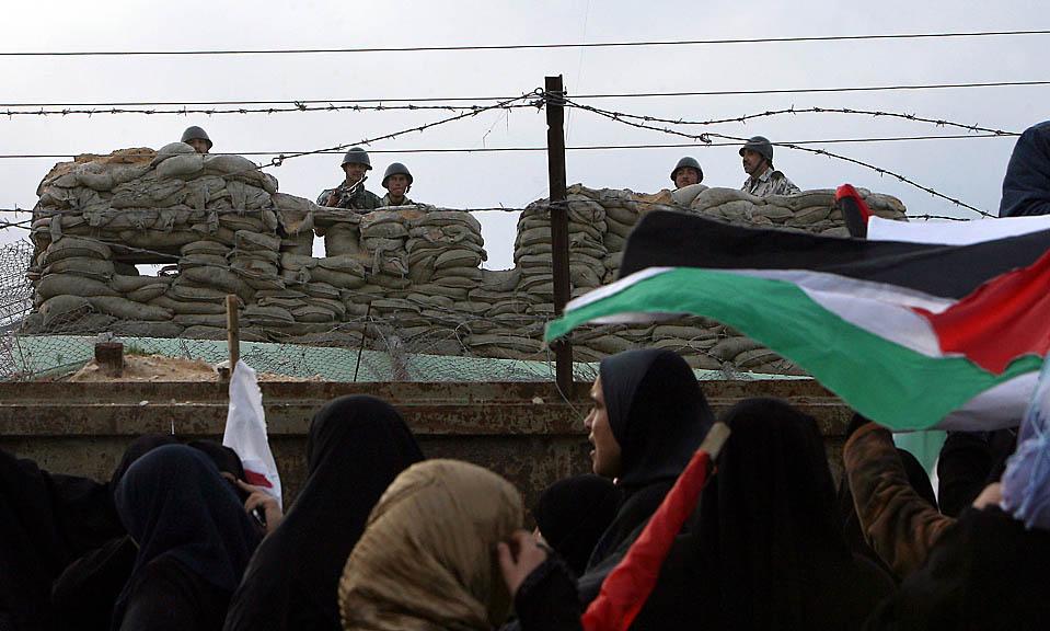 6. Египетские пограничники охраняют свою сторону границы в Рафахе, Сектор Газа. С другой стороны палестинские женщины протестуют против подземного тоннеля, который Египет строит вдоль границы. (Said Khatib/Agence France-Presse/Getty Images)