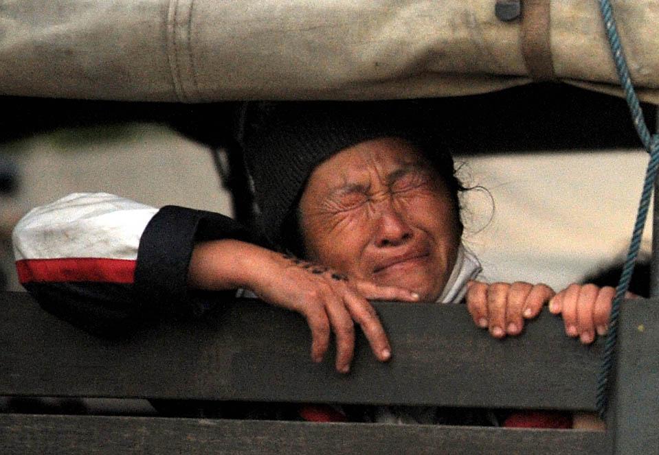 8. Беженка народности хмонг сидит в полицейском грузовике во время операции по депортации более 4000 представителей народности хмонг обратно в Лаос из Фетчабуна, Таиланд. Тайское правительство было раскритиковано за этот шаг. (Pornchai Kittiwongsakul/Agence France-Presse/Getty Images)