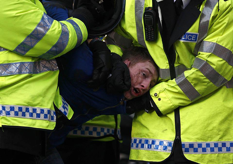 10. Полиция уводит футбольного фаната клуба «Брентфорд» во время матча между его любимой командой и «Чарлтон Атоетик» в Гриффин-парк в Лондоне. (Jed Leicester/Getty Images)