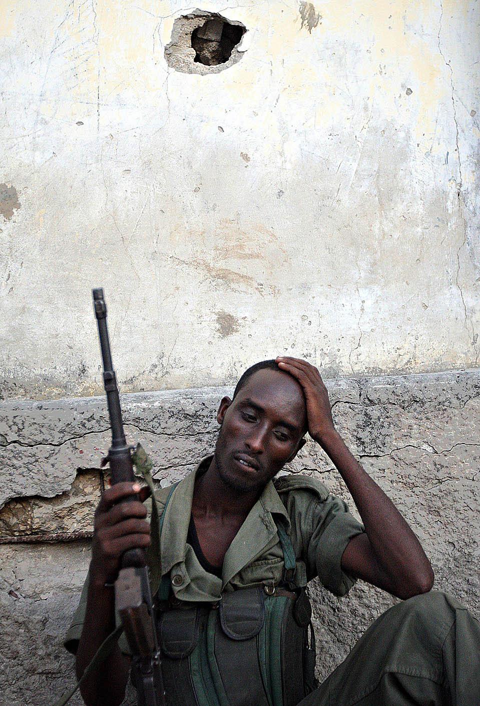 11. Правительственный солдат отдыхает, пока его товарищи участвуют в перестрелке с исламскими боевиками в Могадишо, Сомали. (Mohamed Dahir/Agence France-Presse/Getty Images)
