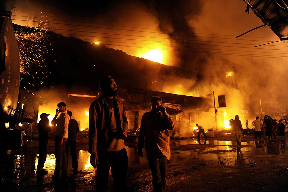2. Владельцы магазинов собрались на рынке в Карачи, который в понедельник подожгли демонстранты. Поджог произошел после взрыва террориста-смертника во время шиитской процессии на празднике Ашура, в результате которого погибло 43 человека. (Asif Hassan/Agence France-Presse/Getty Images)