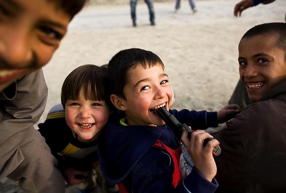 3. Мальчик засунул игрушечный пистолет себе в рот, играя со своими друзьями на одной из улиц Кабула. (Marko Djurica/Reuters)