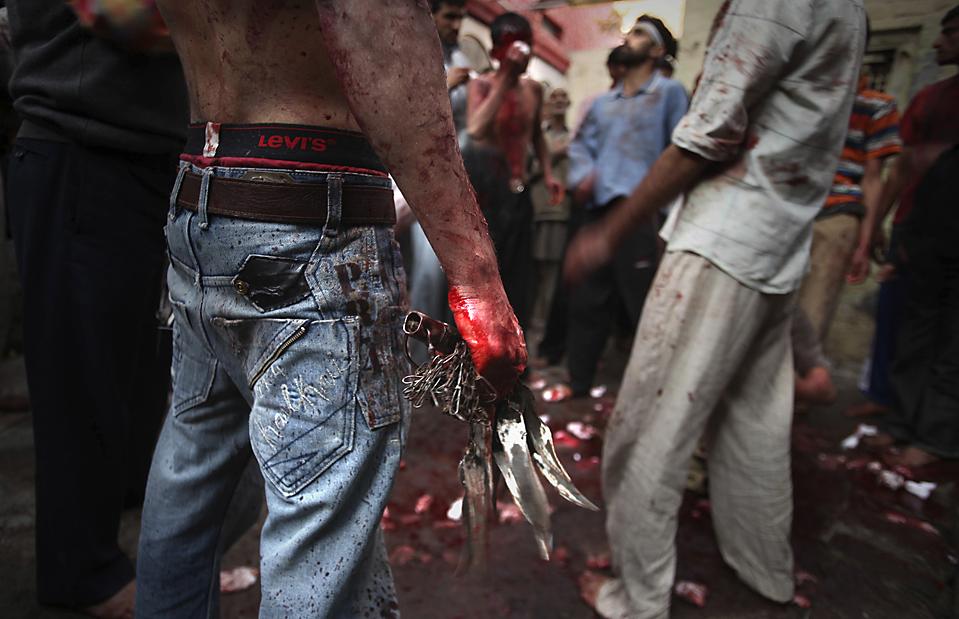 5. Шиитский мусульманин держит ножи, пока другие занимаются самобичеванием у мечети в праздник Ашура в Амритсаре, Индия. (Altaf Qadri/Associated Press)