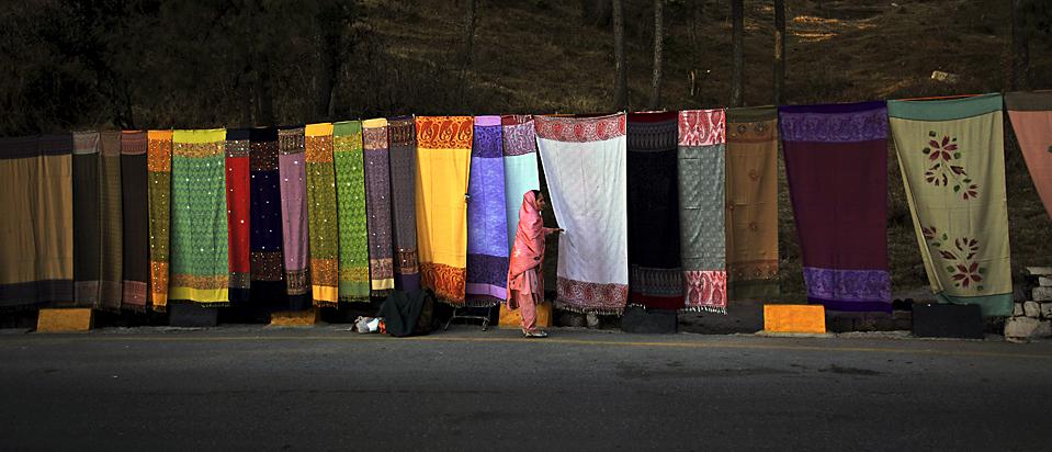 7. Женщина выбирает шаль у лотка вдоль главной дороги в Муррее, Пакистан. (Muhammed Muheisen/Associated Press)