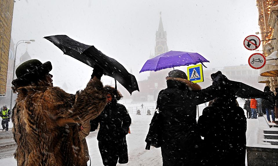 15. Женщины пытаются укрыться от снега под зонтами возле Кремля в Москве. (Dmitry Kostyukov/Agence France-Presse/Getty Images)