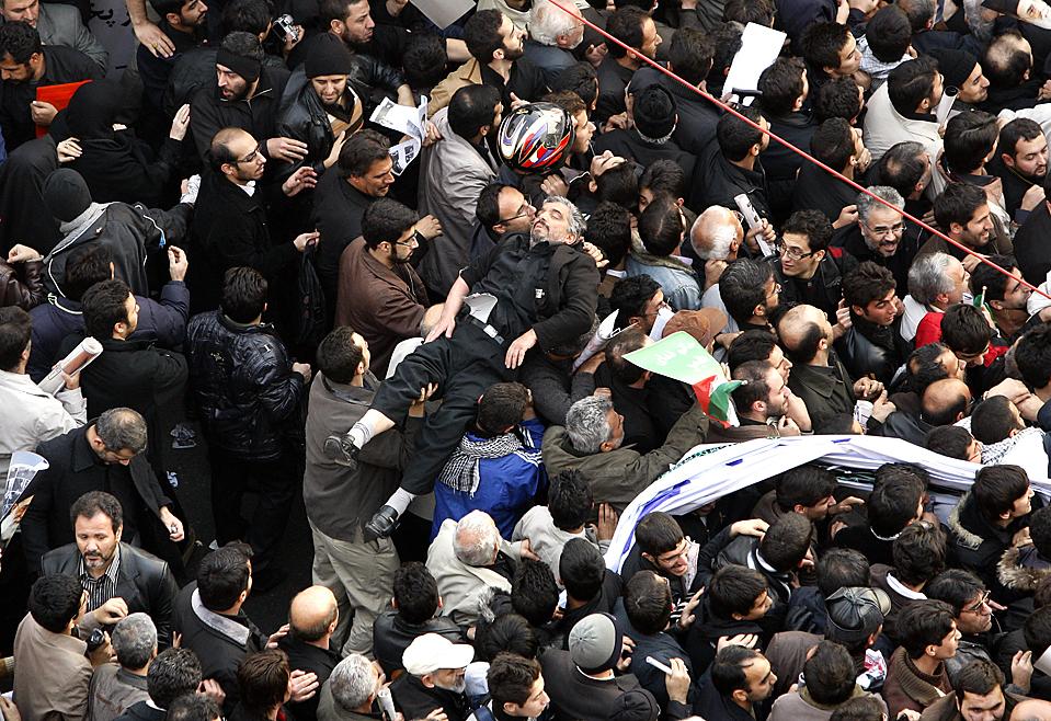 4. Демонстранты несут человека, упавшего в обморок во время правительственного митинга на площади Энкелаб в Тегеране. Десятки тысяч людей пришли на митинги, спонсируемые правительством, некоторые из которых взывали к казни лидеров оппозиции. (Vahid Salemi/Associated Press)