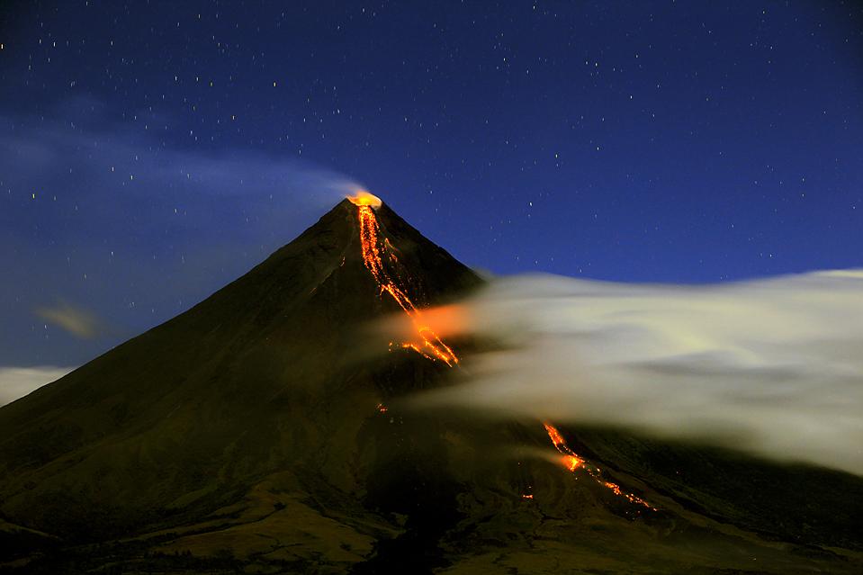 10. Лава вытекает из кратера вулкана Майон в Легазпи, Филиппины. Около 50 000 человек были вынуждены покинуть свои дома на время извержения вулкана. (Bullit Marquez/Associated Press)