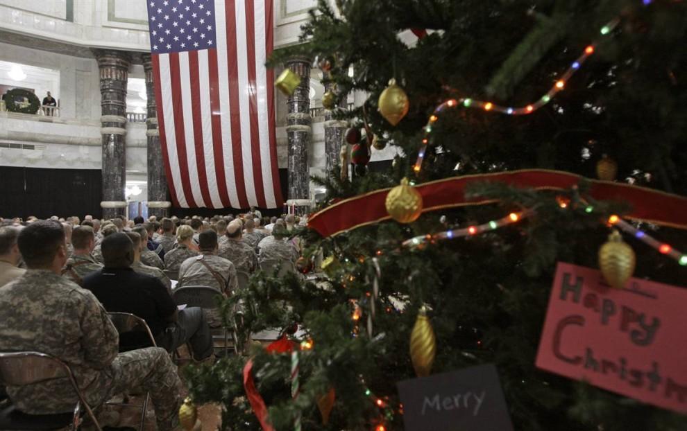 12. Американские солдаты принимают участие в концерте накануне Рождества на военной базе Виктория, расположенной к западу от Багдада. Это уже седьмое Рождество, которое американские солдаты празднуют в Ираке с момента начала событий 2003 года. (Ali al-Saadi/AFP - Getty Images)