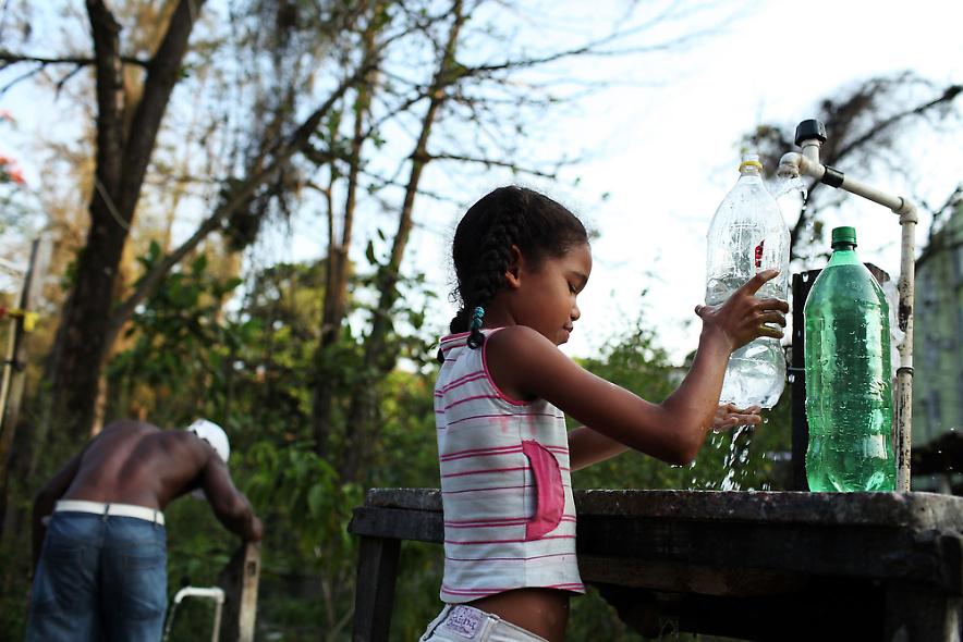 13. Девочка набирает воду в бутылки у уличной колонки – одного из немногих источников воды в бедном районе трущоб Рио-де-Жанейро 2 декабря 2009 года. (Photo by Spencer Platt/Getty Images)