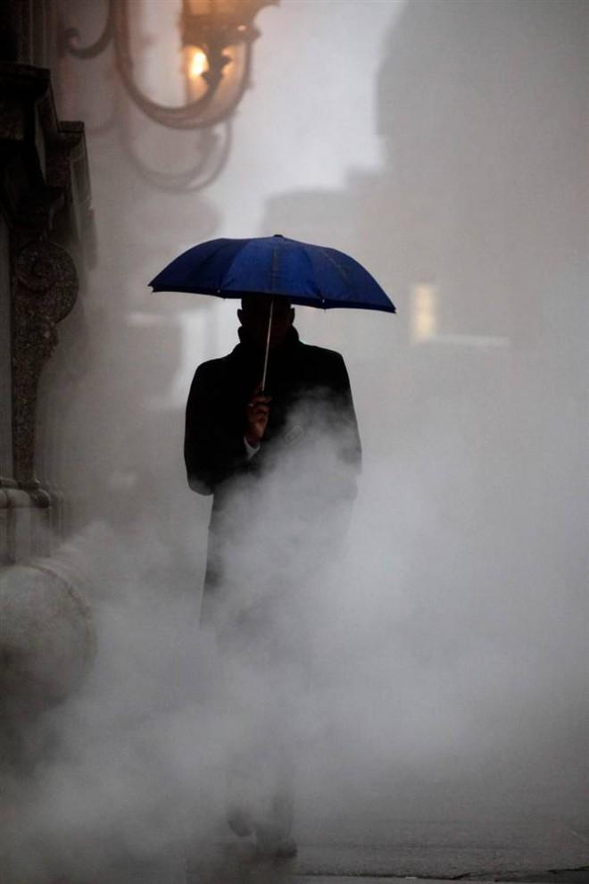10. Человек идет через пар, прячась от дождя под зонтом, в Филадельфии. В Филадельфии и Нью-Йорке по прогнозам ожидался только дождь, но не исключалась вероятность снега и гололеда. (Matt Rourke / AP)