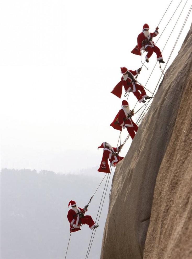 13. Альпинисты из Южной Кореи (сверху вниз) Парк Чанг-Йонг, Ким Хун-Ки, Би Бонг-Ок, Сонг Бок-Хи и Юнг Мюн-Сук в костюмах Санта Клауса взбираются на гору Бухан недалеко от Сеула . (Jeon Heon-Kyun/EPA)