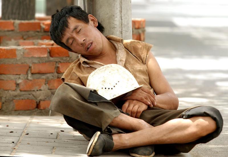 12) Китайский рабочий-мигрант спит во время обеденного перерыва на стройплощадке в центре Пекина 26 июня 2006 года. То, как Китай, уже умудрившийся сократить пропасть между богатыми и бедными и справиться со старением населения, управится с переменами в экономике, покажет способность правительства создавать мегаполисы и предотвращать взрывы безработицы, которые могут навредить социальной стабильности. (UPI Photo/Stephen Shaver)