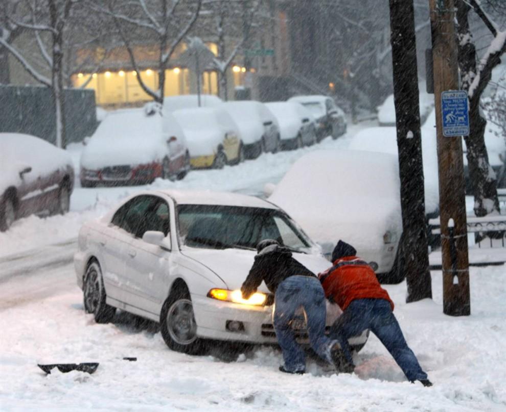 11. Водителю помогают вытолкнуть машину на улицу в Олбани, Нью-Йорк, во время первого в этом сезоне снегопада. (Mike Groll / AP)