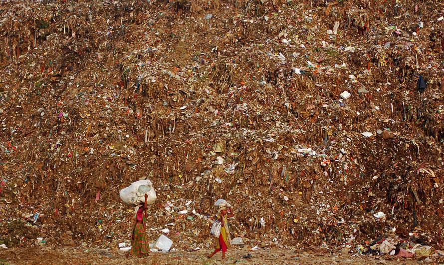 14. Сборщики мусора идут мимо мусорной свалки на окраине Ахмадабада, Индия. (AP Photo/Ajit Solanki)