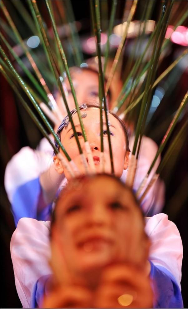 2) Китайские гимнастки показывают номер с балансированием тарелок на палочках. (AFP PHOTO/Leon Neal)