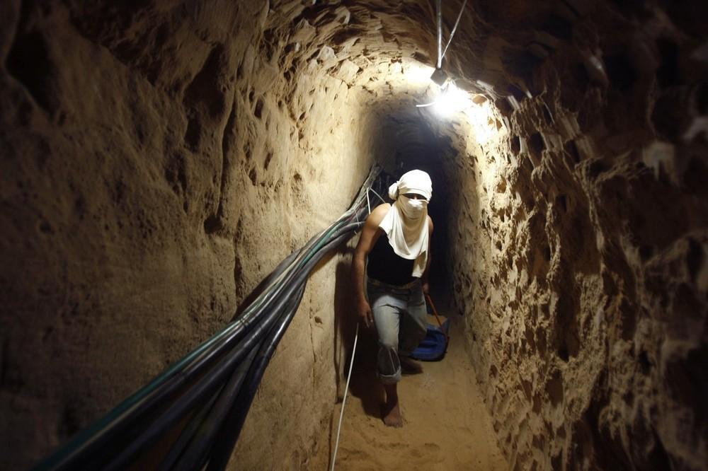 14. Палестинец идет по туннелю, используемому контрабандистами, во время его реконструкции в Рафахе недалеко от границы Газы с Египтом 22 января 2009 года. Сотни палестинцев прибыли на границу Сектора Газа с Египтом, чтобы попытаться восстановить контрабандистские тоннели, разрушенные Израилем во время 22-дневной атаки, и восстановить торговые связи с территориями, где правят члены «Хамаса».
