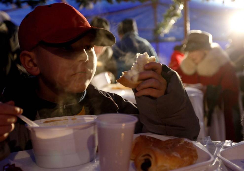 14. Бездомный мальчик ест бесплатную еду на Рождество, раздаваемую городским советом Будапешта . (Laszlo Balogh/Reuters)