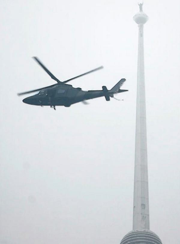 """12) Французский альпинист Ален Роберт, известный как """"Человек-паук"""", стоит на вершине одного из небоскребов Петронас (Petronas Twin Towers) в Малайзии после успешного подъема. (REUTERS)"""