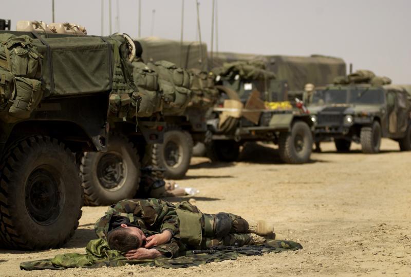 13) Член второй бригады 82-ой воздушно-десантной дивизии дремлет после того, как его конвой прибыл в передовой пункт в южном Ираке для поддержки Операции Иракской Свободы.